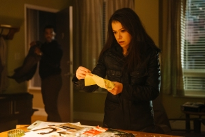 Sarah (Tatiana Maslany) is searching for something in Art's (Kevin Hanchard) apartment