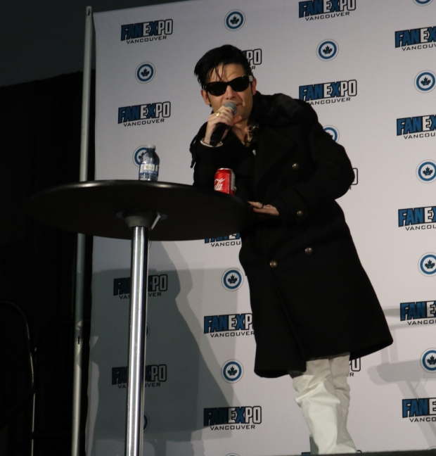 Corey Feldman leans against a high table. He is a Caucasian male with black hair that falls into his face. He is wearing dark sunglasses. He is wearing white pants and a long black coat. He is holding a microphone to his mouth to speak.